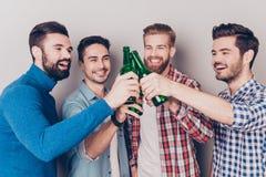 Stäng sig upp ståenden av fyra lyckliga manvänner som klirrar deras glas Royaltyfri Bild