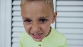 Stäng sig upp ståenden av ilskna 5-6 år gammal pojke över vit dörrbakgrund Ilsken rolig framsida av den lilla ungen som ser stock video