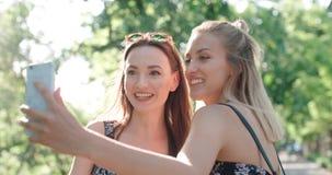 Stäng sig upp ståenden av två unga gladlynta flickor som har gyckel och gör selfie, utomhus Arkivbilder