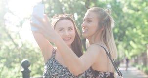 Stäng sig upp ståenden av två unga gladlynta flickor som har gyckel och gör selfie, utomhus Arkivbild