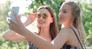 Stäng sig upp ståenden av två unga gladlynta flickor som har gyckel och gör selfie, utomhus Fotografering för Bildbyråer
