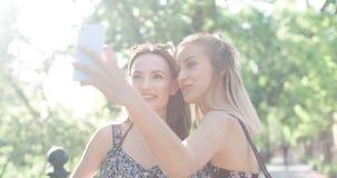 Stäng sig upp ståenden av två unga gladlynta flickor som har gyckel och gör selfie, utomhus Royaltyfria Bilder