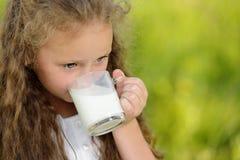 Stäng sig upp ståenden som den förtjusande lockiga flickan som dricker ett exponeringsglas av, mjölkar utomhus- sommar arkivbilder
