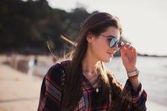 Stäng sig upp strandståenden av den gladlynta blonda hipsteren Lös flicka på sommarstranden med solglasögon, hipsterflickastil Fotografering för Bildbyråer