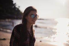 Stäng sig upp strandståenden av den gladlynta blonda hipsteren Lös flicka på sommarstranden med solglasögon, hipsterflickastil Arkivbilder