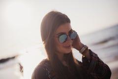 Stäng sig upp strandståenden av den gladlynta blonda hipsteren Lös flicka på sommarstranden med solglasögon, hipsterflickastil Arkivbild