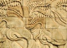 Stäng sig upp stuckaturen sned väggen som visar elefanter royaltyfri fotografi