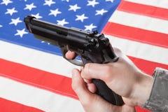 Stäng sig upp studioskott av vapnet i hand med flaggan på bakgrund - Amerikas förenta stater Arkivbild
