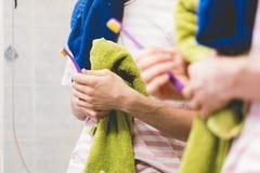 Stäng sig upp tandborsten och handduken för person den hållande i badrum nära en spegel royaltyfri foto