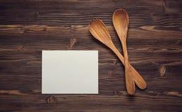 Stäng sig upp träskedar och tomt papper på träbräde Arkivfoto