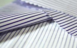 Stäng sig upp tunn purpurfärgad linje för texturtyg och vit av skjortan Arkivfoto