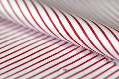 Stäng sig upp tunn röd linje för texturtyg och vit av skjortan Royaltyfri Foto