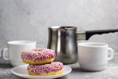 Stäng sig upp två donuts på koppar för ett kaffe för platta suddiga royaltyfri fotografi