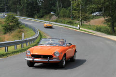 Stäng sig upp två klassiska orange italienska sportbilar på vägen Arkivbild