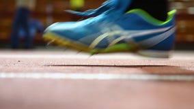 Stäng sig upp ultrarapidvideomaterial av benet av en löpare i gymnastikskor stock video