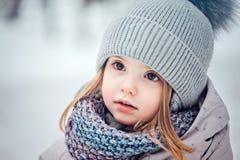Stäng sig upp vinterståenden av den förtjusande litet barnflickan i snöig skog arkivbilder