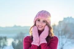 Stäng sig upp vinterståenden av en ung le kvinna i en rosa hatt Fotografering för Bildbyråer