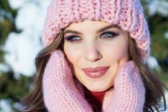 Stäng sig upp vinterståenden av en ung le kvinna i en rosa hatt Royaltyfri Foto