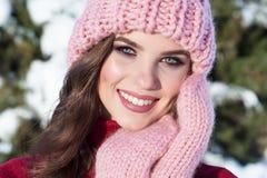 Stäng sig upp vinterståenden av en ung le kvinna i en rosa hatt Arkivbild
