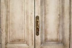 Stäng sig upp yttre sikt av en forntida trägaragedörr Metalliska beståndsdelar, handtaget och nyckelhålet är synliga Målade vit o Arkivbild
