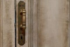 Stäng sig upp yttre sikt av en forntida trägaragedörr Metalliska beståndsdelar, handtaget och nyckelhålet är synliga Målade vit o Royaltyfria Bilder