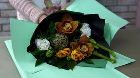 Stäng upp av blomsterhandlaresjalar en bukett i grönt inpackningspapper Kronärtskocka orange orkidé, vit nejlika, skimmia stock video