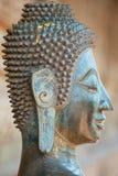 Stäng upp av en framsida av en forntida kopparBuddhastaty förutom den Hor Phra Keo templet i Vientiane, Laos arkivfoton