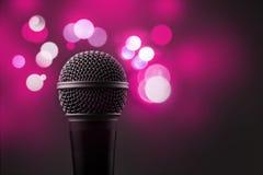 Stäng upp av en yrkesmässig mikrofon med rosa suddiga ljus I Arkivbild