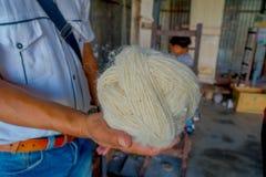 Stäng upp av ett maninnehav i hans hand per stycke av ull som arbetar på för whoolsjal för vävstol fabriks- kläder i Nepal Arkivbild