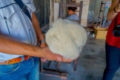 Stäng upp av ett maninnehav i hans hand per stycke av ull som arbetar på för whoolsjal för vävstol fabriks- kläder i Nepal Royaltyfria Bilder