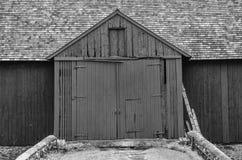 Stäng upp av ett svart en vit ladugård med stora dubbla dörrar royaltyfria foton