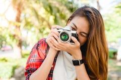 Stäng upp av ungt asiatiskt kvinnaknäpp hennes kamera som är utomhus- och tycks om hennes stadslivsstil på helg arkivbilder