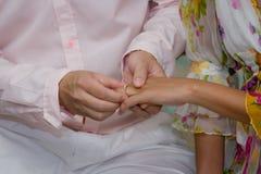 Stäng upp brudgummen Put vigselringen på brud Royaltyfri Bild