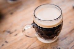 Stäng upp det bästa första personsiktsfotoet av den manliga rymmande bruna svarta tyska koppen för öl för naturligt exponeringsgl arkivfoton