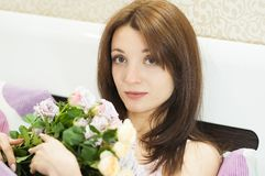 Stäng upp inomhus ståenden av den nätta flickan med buketten av blommorna som tidigt på morgonen ligger på sängen royaltyfri bild