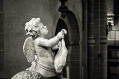 Stäng upp svartvitt av en ängel som snidas in i stenen arkivfoton