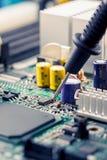 Stäng upp - teknikerteknikern som mäter moderkortet för brädet för multimeterdatorströmkretsen arkivfoton