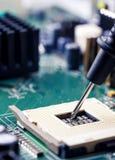 Stäng upp - teknikerteknikern som mäter moderkortet för datoren för multimeterCPU-håligheten royaltyfri fotografi