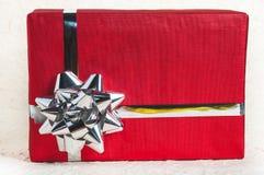 Stäng upp till den röda gåvaasken med bandet, och garnering för jul planlägger Royaltyfri Foto