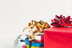 Stäng upp till den röda gåvaasken med bandet, och garnering för jul planlägger Royaltyfri Bild