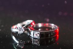 Stäng upp till vigselringar med röd belysning som betyder att visa till förhållande av förälskelse, det tecknet för ` s ett löfte Arkivbild