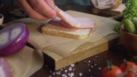 Stäng upp videoen av framställning av smörgåsen med skivad skinka, och grönsaker, kock tillfogar rökt skinka till smörgåsen som g stock video