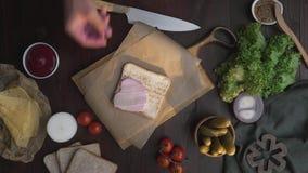 Stäng upp videoen av framställning av smörgåsen med skivad skinka, och grönsaker, kock tillfogar rökt skinka till smörgåsen som g arkivfilmer
