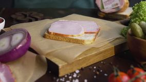 Stäng upp videoen av framställning av smörgåsen med skivad skinka, och grönsaker, kock tillfogar rökt skinka till smörgåsen som g lager videofilmer