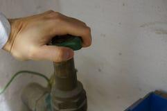 Stäng vattenkranen - händer på hjulet Royaltyfri Fotografi