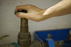 Stäng vattenkranen - händer på hjulet Fotografering för Bildbyråer