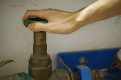 Stäng vattenkranen - händer på hjulet Royaltyfri Foto
