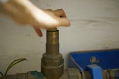 Stäng vattenkranen - händer på hjulet Royaltyfri Bild