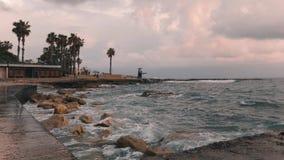 Stäng vyn över stadsstranden. Strand vid stormväder. Turistområde med strandpromenad vid storm. Stora sjövågor som kraschar  stock video