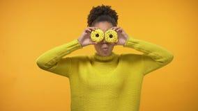 Stängande ögon för gladlynt Afro--amerikan flicka med donuts och att ha gyckel, bakgrund stock video